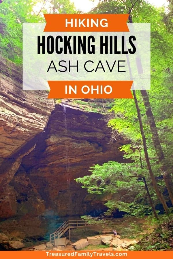 Large horse shoe shaped cave surrounded by bright green trees with the words Hocking Hills Ash Cave in black text on a white background on top