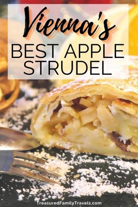 Layers of apples wrapped in a pastry crust topped with powdered sugar on a plate with a fork under a white overlay with black text reading Vienna's best apple strudel