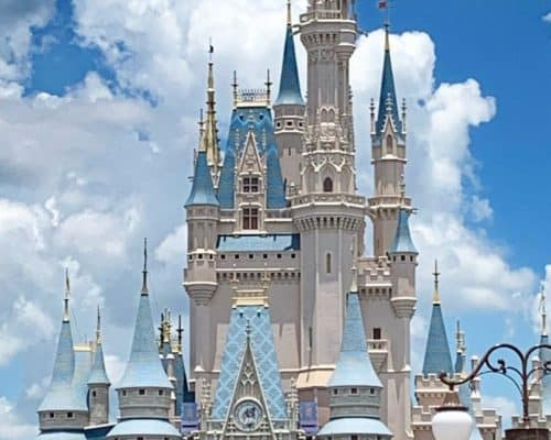 Beige and light blue castle at Disney World with blue sky and clouds in the back