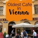 People dining outside on tables under large umbrellas against a yellow stucco building with a text overlay that says 'oldest cafe in vienna'