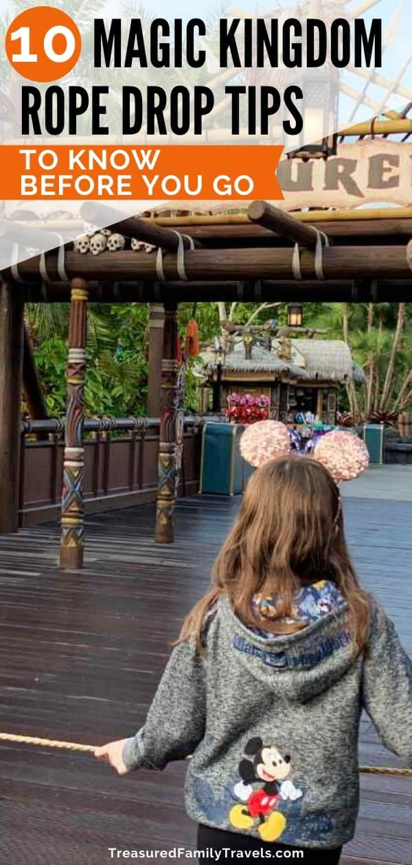 Girl in gray sweatshirt with Mickey Mouse on the back standing in front of a rope looking towards a sign called Adventureland
