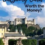 White fortress atop a hill overlooking gardens with greenery and statues; blue sky with black words saying 'Is the Salzburg Card worth the money'