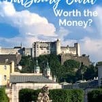 White fortress atop a hill overlooking gardens with greenery and statues; blue sky with white words saying 'Is the Salzburg Card worth the money'