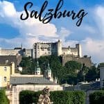 White fortress atop a hill overlooking gardens with greenery and statues; blue sky with black words saying '48 hours in Salzburg'