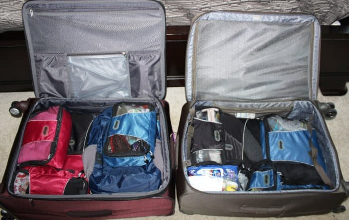Two suitcases side by side on the floor open with packing cubes in them.