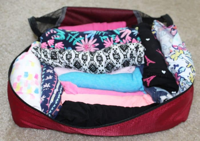 Rolled clothes in a pink packing cube
