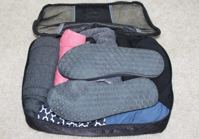 Rolled clothes and shoes in a black packing cube with shoes on top