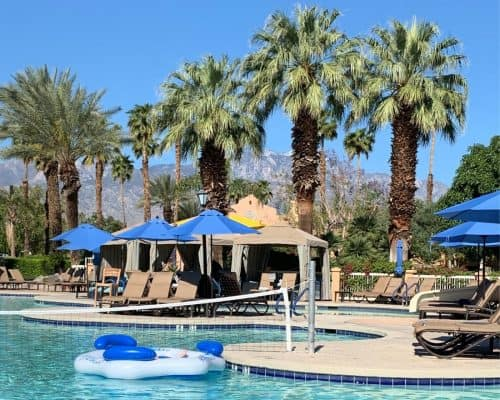Swimming pool with beach umbrellas and cabanas under blue skies in Palm Springs, CA