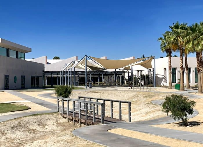 Outside view of white building housing the Children's Discover Museum with Palm Trees and wooden bridge in front of parched grass