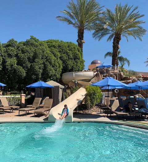 Little girl coming down a slide into a pool of water with trees and beach umbrellas in the background at The Westin Mission Hills Resort