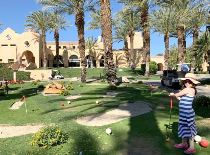 Girl in blue striped dress posing with putter on a mini golf course outside The Westin Mission Hills resort