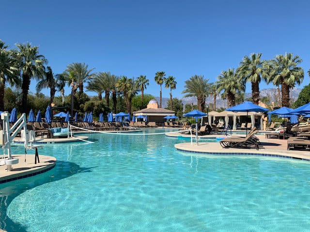 Gorgeous pool area with blue umbrellas, palm trees and blue skies against the mountains in Palm Springs