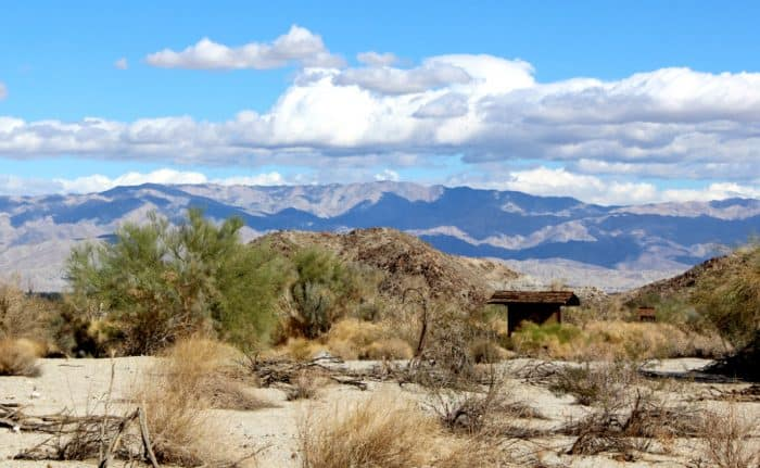 Desert sand, bluffs and trails in front of the mountains with blue sky and clouds at The Living Desert