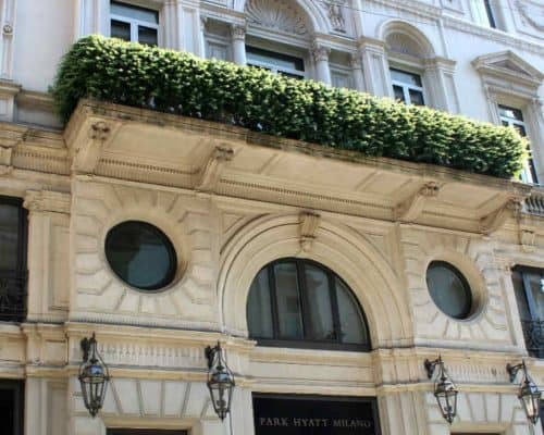 Entrance to the Park Hyatt Milan hotel - white stone with greenery on top of the entrance area