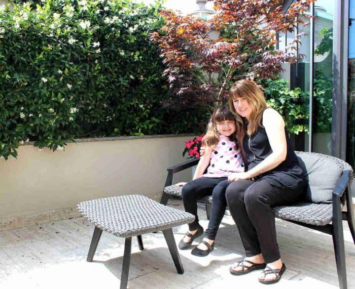 Mother and daughter sitting on a wicker couch on a terrace at the Park Hyatt Milan