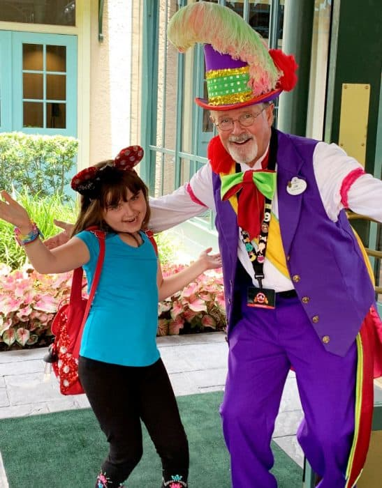 Girl in blue shirt and black leggings with mickey ears posing with a Jester in purple and red at the entrance to Port Orleans French Quarter