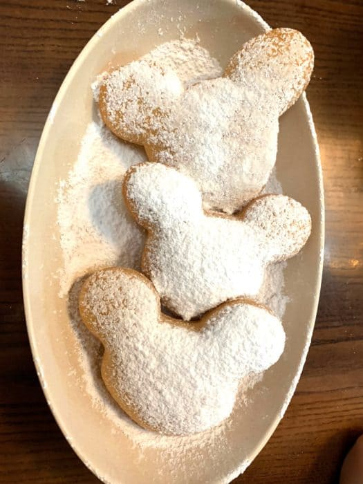Three Mickey Mouse head fried beignets covered in powdered sugar in a beige ceramic oval dish served at Port Orleans French Quarter.