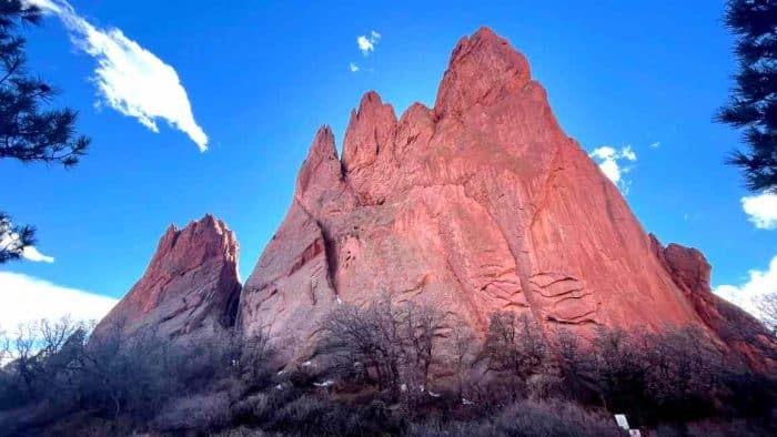 Tall, red rock formation against a deep blue sky.