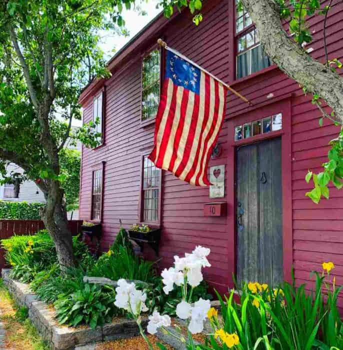 Dark red house with an American flag above the doorway and white and yellow flowers surrounding the house.