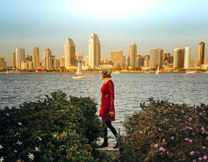 Woman in red dress standing between two green bushes in front of an ocean with a view of the San Diego skyline behind her