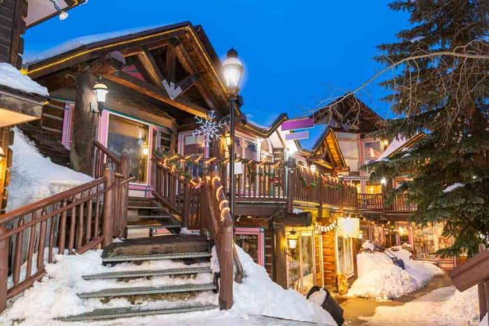 Cute street of shops in Breckenridge decorated with holiday decor and snow piles.