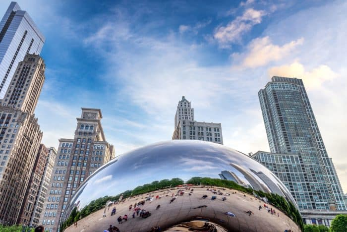 Large curved mirrored 'bean' in front of high-rise buildings in Chicago's Millenium Park