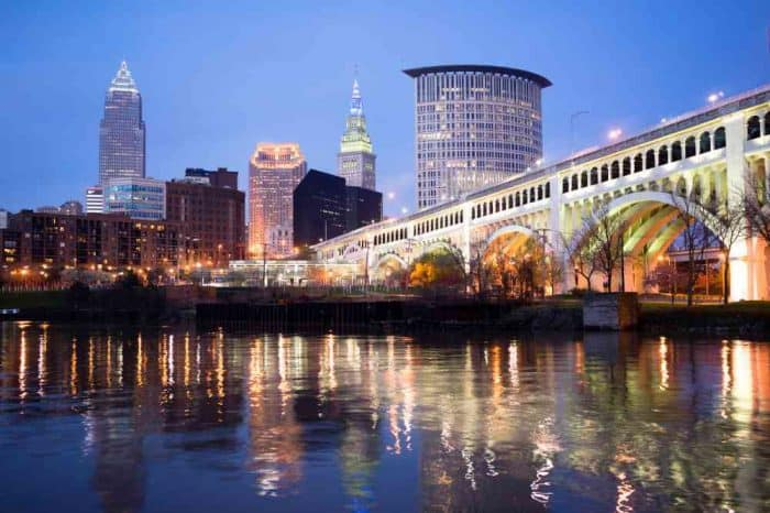 Nighttime image of the Cleveland waterfront with a lit up white bridge in the foreground and several tall buildings in the back.