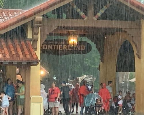 Group of people taking cover under a Frontierland sign at Disney World due to the rain storm.