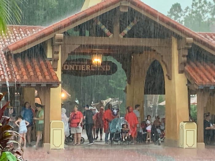 Large group of people taking cover under a sign that reads 'Frontierland' as it's raining at Disney World.