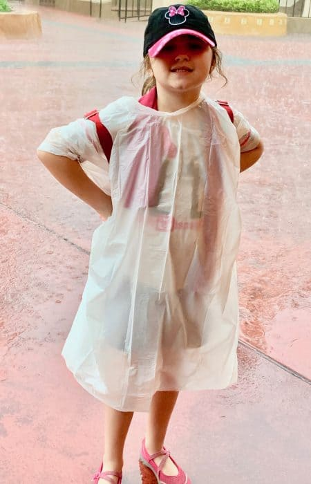 Little girl wearing a white poncho and baseball cap in the rain at Disney World