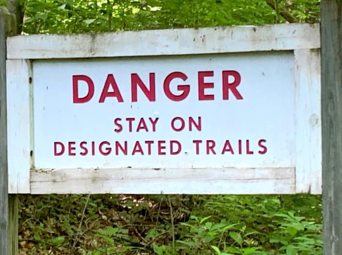 White wooden sign with red letters in Rockbridge State Nature Preserve that say Danger Stay on Designated Trails