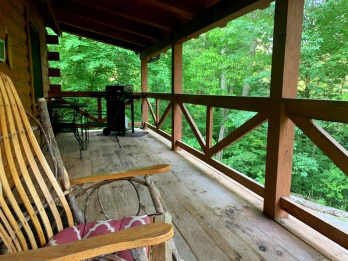 Wooden deck with brown railings and a rocking chair looking into the green forest
