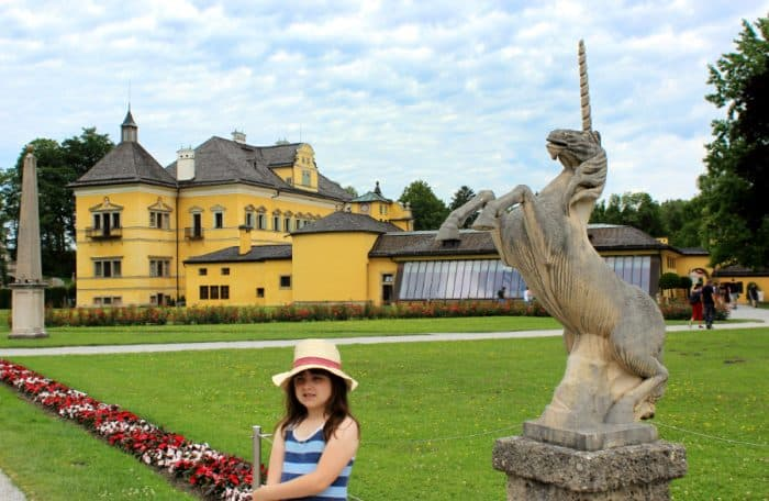 Little girl on the green lawn next to a unicorn statue with a yellow palace in the background