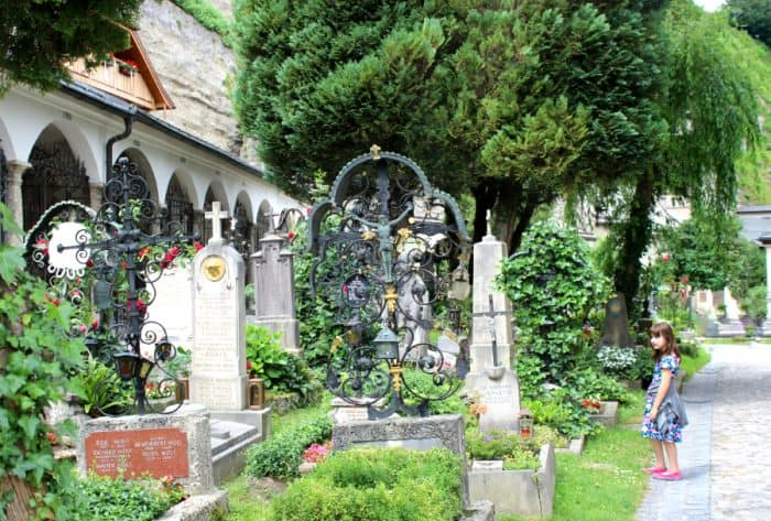 Green trees and flowers stand over and around tall tombstones at St Peter's cemetery in Salzburg