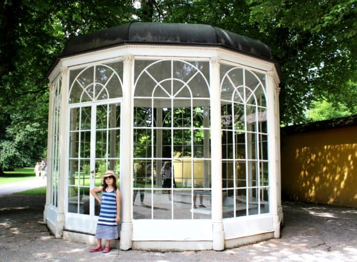 White enclosed gazebo under a large green shade tree with a young girl standing in front