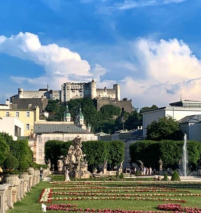 Gardens of red and white flowers amid green grass, statues and water fountains give way to the white Hohensalzburg Fortress at the top of the hill