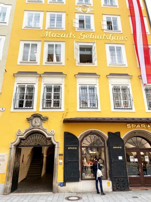 Yellow building with four rows of white windows, some with bars on them and an entrance door opened; words Mozart's house written in German on the house
