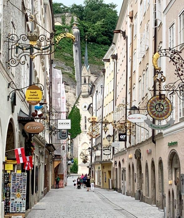 Narrow shopping street with stone walkways and lavishly decorated store signs leading to a mountain with a lift to the top