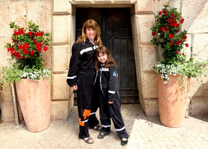 Woman and child dressed in black miner's wear posing in front of a wooden door flanked by a large terracotta pot filled with red and white flowers on each side