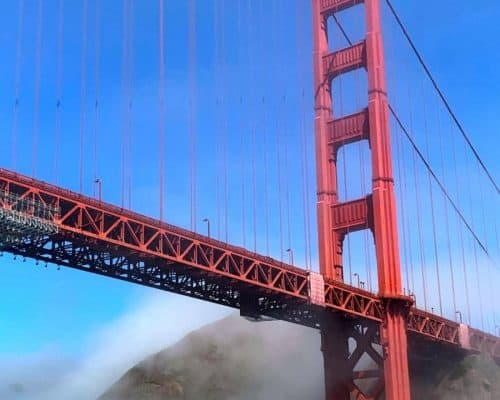 Blue sky, fog over a mountain and a red steel bridge.
