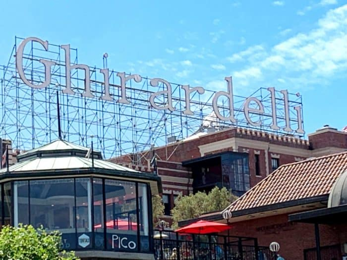 Large white lettering reading Ghirardelli on top of brown and glass buildings