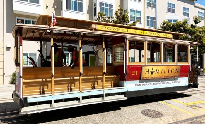 Open air trolley car with lettering Powell & Mason Sts on top