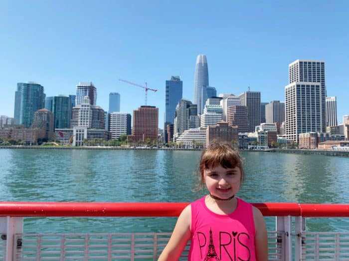 Girl in pink tank top standing next to a red boat railing with the San Francisco skyline in background.