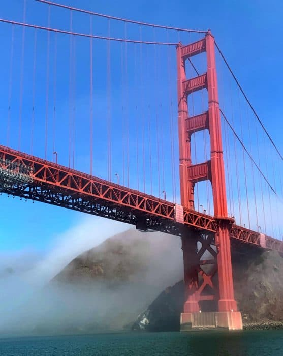 Red steel bridge going from a fog surrounded mountain to water amid bright blue sky