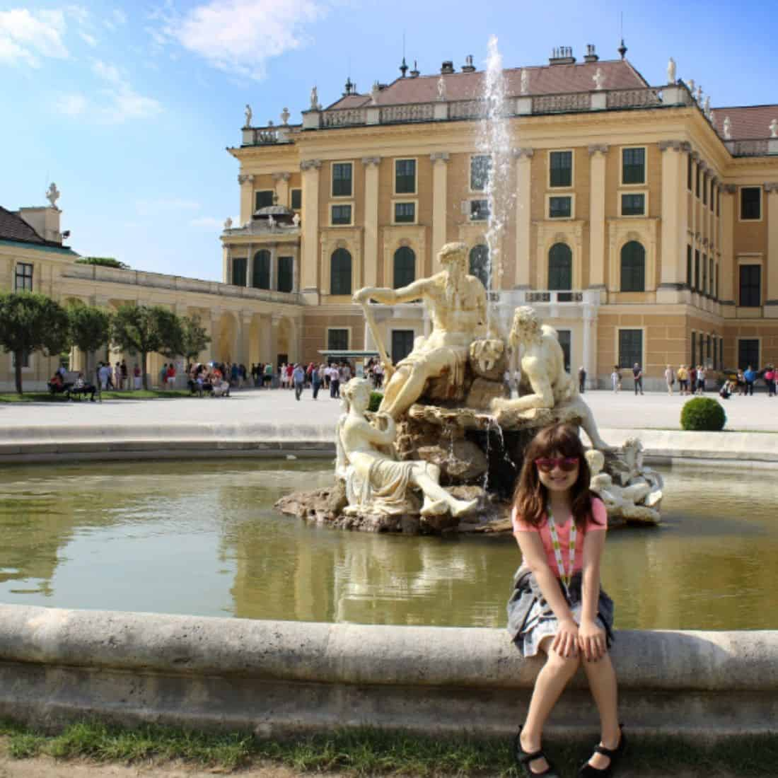 Little girl sitting on the edge of a fountain in front of a massive orange and cream palace