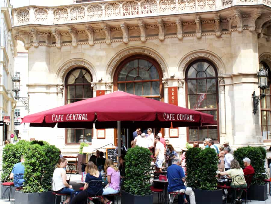 People sitting at tables under a large maroon umbrella that reads Cafe Central in front of a stately white building with large windows; take time to experience cafe life with kids in Vienna