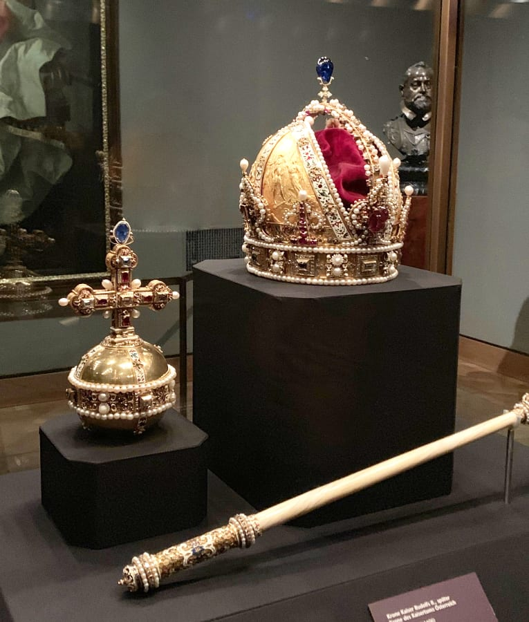 Gold crown on a brown pedestal with a gold staff laying in front of it both behind glass at the Imperial Treasury