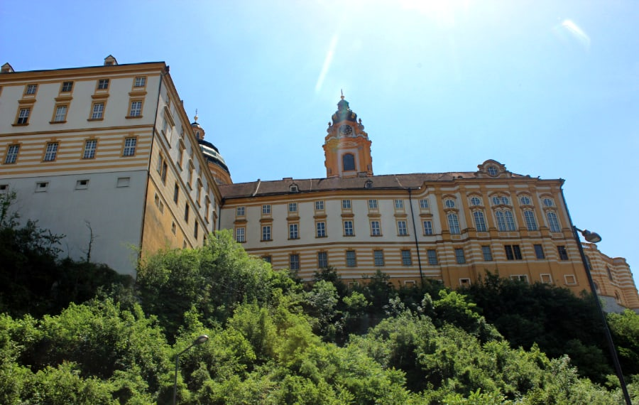 Looking up at a yellow and cream large building with a clock tower in the center; greenery surrounds the hilltop