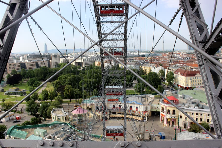 Looking out at steel structure carrying red cable cars around a wheel at a children's park in Vienna