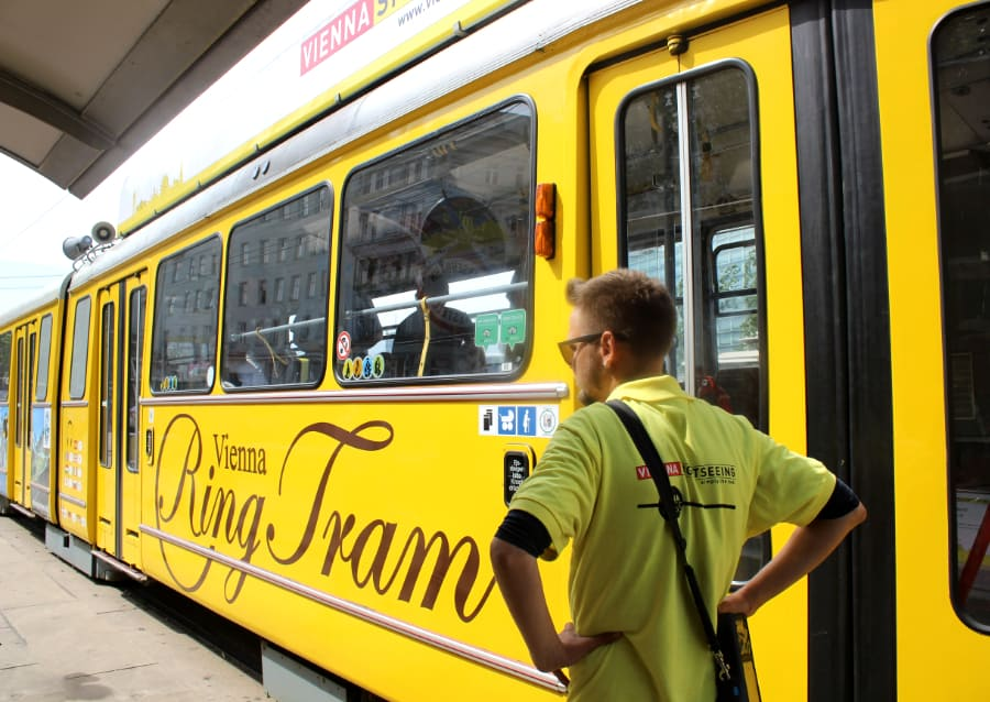 Large bright yellow tram with a man standing at the doors with writing Vienna Ring Tram on the side